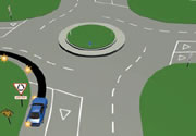 Picture of a car signalling left at a multi-laned roundabout