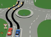 Picture of a car driving straight through a multi-laned roundabout