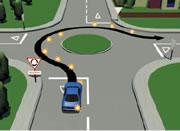 Picture of a car signalling right at a single-laned roundabout